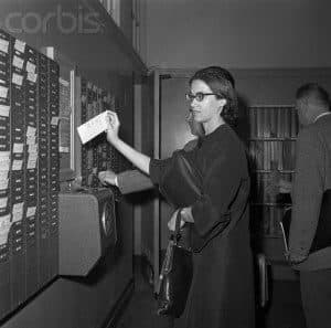12 Apr 1962, New York, New York, USA --- An unidentified teacher punches a time clock as she reports back to Stuyvesant High School following a one-day walkout by nearly 20,000 public school teachers. The teachers returned to their classrooms after a State Supreme Court injunction forbidding the strike was issued. --- Image by © Bettmann/CORBIS